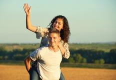 Счастливые молодые пары идут на концепцию страны внешнюю, романтичную людей, сезон лета, катание девушки на задней части человека Стоковое фото RF