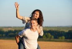 Счастливые молодые пары идут на концепцию страны внешнюю, романтичную людей, сезон лета, катание девушки на задней части человека Стоковые Фотографии RF