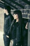 Счастливые молодые пары моды flirting рядом с кирпичной стеной Стоковые Фотографии RF