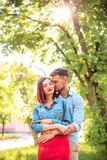 Счастливые молодые пары на парке стоя и смеясь над на яркий солнечный день Стоковые Изображения