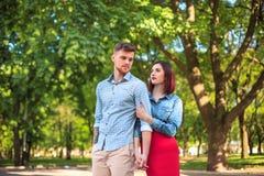 Счастливые молодые пары на парке стоя и смеясь над на яркий солнечный день Стоковое Изображение RF