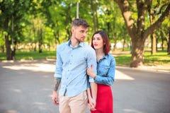 Счастливые молодые пары на парке стоя и смеясь над на яркий солнечный день Стоковые Фотографии RF
