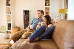 Счастливые молодые пары ослабляя на кресле стоковые фото