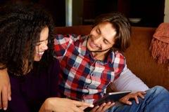 Счастливые молодые пары ослабляя дома с цифровой таблеткой Стоковые Изображения RF
