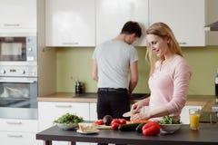 Счастливые молодые пары подготавливая салат Стоковая Фотография RF
