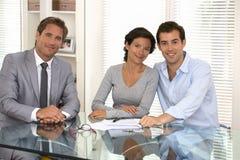 Счастливые молодые пары подписывая финансовый контракт, смотря камеру Стоковое фото RF