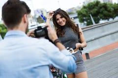 Счастливые молодые пары принимая фото в улице стоковое изображение