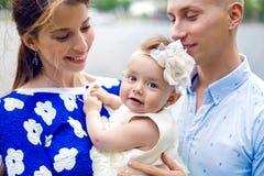 Счастливые молодые пары при ребёнок стоя в воде Стоковая Фотография