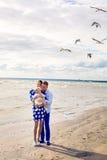 Счастливые молодые пары при ребёнок стоя в воде Стоковые Изображения