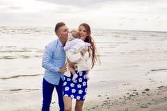 Счастливые молодые пары при ребёнок стоя в воде Стоковое Фото