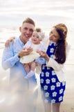 Счастливые молодые пары при ребёнок стоя в воде Стоковое Изображение