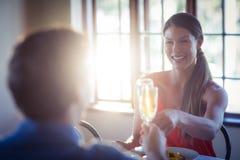 Счастливые молодые пары провозглашать каннелюры шампанского пока имеющ обед Стоковая Фотография
