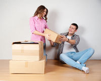 Счастливые молодые пары распаковывая или коробки упаковки и двигая в новый дом Стоковые Изображения RF