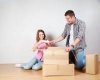 Счастливые молодые пары распаковывая или коробки упаковки и двигая в новый дом Стоковые Фотографии RF
