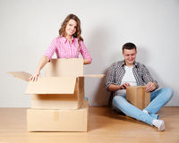 Счастливые молодые пары распаковывая или коробки упаковки и двигая в новый дом Стоковые Изображения