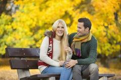 Счастливые молодые пары сидя на скамейке в парке во время осени Стоковые Изображения RF