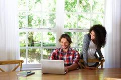 Счастливые молодые пары сидя на таблице с компьтер-книжкой Стоковые Фотографии RF