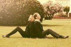 Счастливые молодые пары сидя на траве в городе паркуют Стоковая Фотография RF