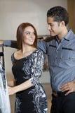 Счастливые молодые пары смотря один другого пока ходящ по магазинам в бутике моды Стоковые Изображения