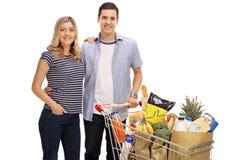 Счастливые молодые пары с магазинной тележкаой вполне бакалей стоковое фото rf