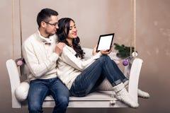 Счастливые молодые пары с планшетом на качании Стоковое фото RF
