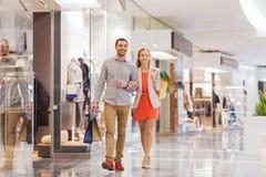 Счастливые молодые пары с хозяйственными сумками в моле стоковое изображение rf