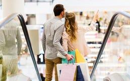 Счастливые молодые пары с хозяйственными сумками в моле Стоковое Изображение