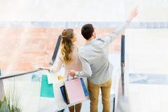 Счастливые молодые пары с хозяйственными сумками в моле Стоковые Изображения RF