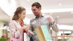 Счастливые молодые пары с хозяйственными сумками в моле сток-видео