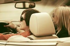 Счастливые молодые пары управляя обратимым автомобилем стоковое фото rf