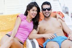 Счастливые молодые пары усмехаясь, обнимая и ослабляя на бассейне Стоковые Фотографии RF