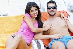 Счастливые молодые пары усмехаясь, обнимая и ослабляя на бассейне Стоковое Изображение