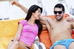 Счастливые молодые пары усмехаясь, обнимая и ослабляя на бассейне Стоковое фото RF