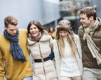 Счастливые молодые друзья идя совместно outdoors Стоковая Фотография