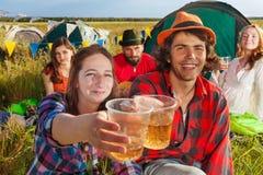 Счастливые молодые друзья лязгая стекла на располагаться лагерем Стоковые Изображения RF