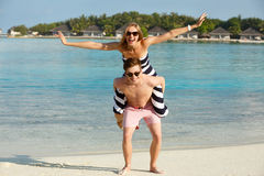 Счастливые молодые симпатичные пары имеют потеху и ослабляют на пляже Человек держит самолет показа женщины на его назад Бунгала  Стоковые Фото