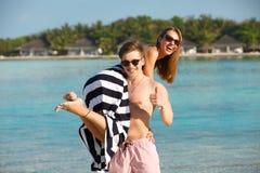 Счастливые молодые симпатичные пары имеют потеху и ослабляют на пляже Человек держит женщину на его плече Бунгала спа-курорта Стоковое фото RF