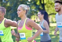 Счастливые молодые спортсмены участвуя в гонке номера значка острословия Стоковые Изображения