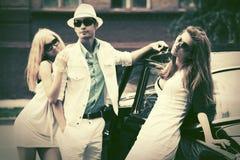 Счастливые молодые люди моды рядом с ретро автомобилем Стоковая Фотография RF