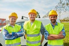 Счастливые мужские построители в высоких видимых жилетах outdoors Стоковые Фотографии RF