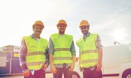 Счастливые мужские построители в высоких видимых жилетах outdoors Стоковые Изображения