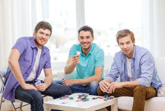 Счастливые 3 мужских друз играя покер дома Стоковые Изображения