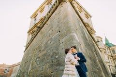 Счастливые новобрачные целуют около стен старого дворца Взгляд обратной стороны Стоковые Фото