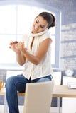 Счастливые ногти опиловки девушки в офисе Стоковая Фотография RF