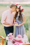 Счастливые носы молодой женщины и человека целуя держа торт украшенный с розовыми цветками outdoors Стоковое Фото