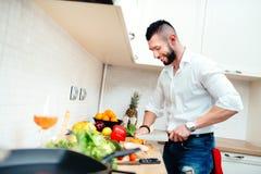 Счастливые овощи вырезывания человека для салата или супа Молодой профессионал хорошо одел кашевара подготавливая еду в новой кух стоковые фото