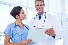 Счастливые доктора держа доску сзажимом для бумаги Стоковые Изображения RF