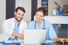 Счастливые доктора используя компьтер-книжку пока обсуждающ на столе Стоковое Фото