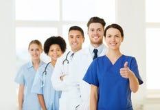 Счастливые доктора показывая большие пальцы руки вверх на больнице Стоковое фото RF