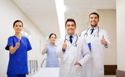 Счастливые доктора показывая большие пальцы руки вверх на больнице Стоковая Фотография RF